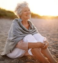 Happy retired woman wearing shawl sitting relaxed on sand at the beach. Senior caucasian woman sitting on the beach outdoors