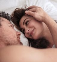 Romantic young couple lying together on bed. Man and woman looking at each other passionately.
