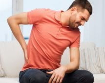 people, healthcare and problem concept - unhappy man suffering from pain in back or reins at home