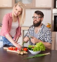 Beautiful young couple slicing vegetables for salad in a modern kitchen