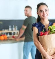 Young couple in the kitchen , woman with a bag of groceries shop