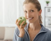 Confident smiling woman eating an apple after working out, fitness and healthy diet concept